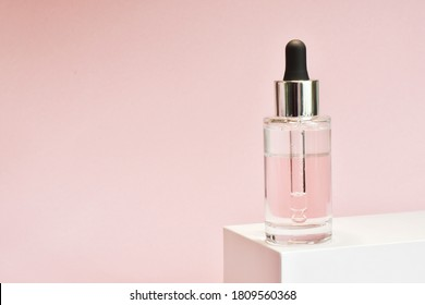 Bottle of moisturizing face oil on a white stand on a pink background. A professional product for a perfect complexion. Women's accessories, cosmetic base. Copy space.