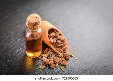 A bottle of myrrh essential oil with myrrh resin on a black slate background