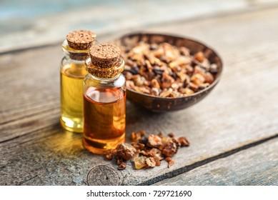 A bottle of myrrh essential oil with myrrh resin on a wooden background