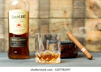 bottle of Oakheart Bacardi, next to a filled crystal glass, ashtray and cigar, all on a wooden, rustic background. Renningen, Germany, 20.10.2018