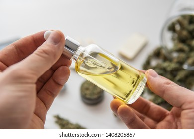 bottle of oil Cannabis in pipette in hand, hemp product, medical marijuana concept, CBD cannabis OIL on white background, close up,