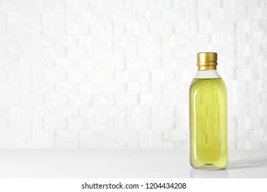 Bottle of oil on table against light background. Space for text