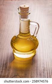 bottle of oil on vintage wooden board food and drink concept