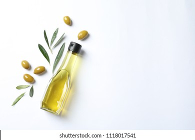 Bottle with oil and ripe olives on white background