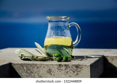 bottle with olive oil and fresh olive fruits on blue sky background