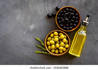 Bottle of olive oil with green and black olives, top view