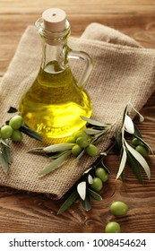 bottle of olive oil and green olives on wooden background