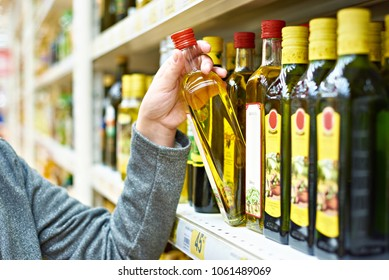 Bottle of olive oil in the hand of the buyer at the grocery store