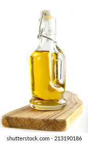bottle of olive oil on wooden board. on white