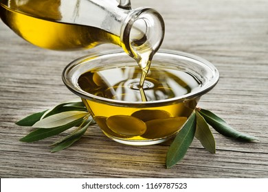 Bottle of Olive oil pouring in a glass bowl with olives