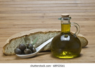 A bottle with olive oil, some bread and some olives in a spoon.