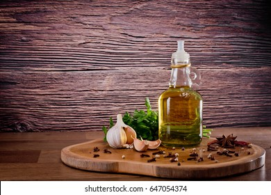 Bottle with olive oil with spices on a wooden background, cloves of garlic and parsley. Backgrounds for the kitchen.