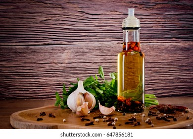 Bottle with olive oil with spices on a wooden background, cloves of garlic and parsley. Backgrounds for the kitchen. Close-up.