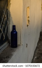 Bottle on a window sill during sunset.