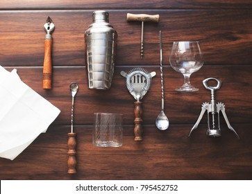 Bottle openers, corkscrew and other barware and mixology supplies in flatlay on wooden table
