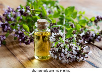 A bottle of oregano essential oil with blooming oregano twigs on a wooden background