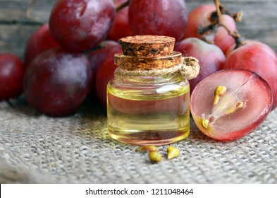 Bottle of organic grape seed oil for spa and bodycare and fresh ripe grapes berries on old wooden table.Healthy food,Bio,Eco products concept.