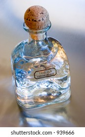 Bottle of Patron Silver Tequila on a reflective metal surface.