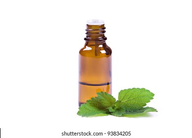 bottle of peppermint oil and fresh mint isolated on white