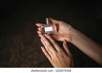 Bottle perfume female hand. Young woman holding bottle of perfume. Fashionable perfumes in hands of women. Girl sprays perfume. Beautiful women's hands.