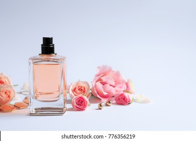 Bottle of perfume with flowers on white background