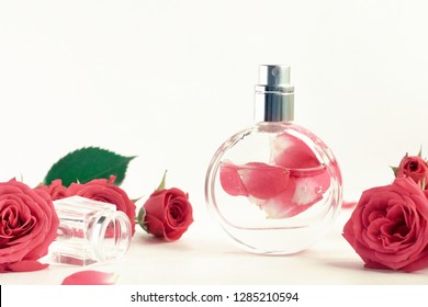 Bottle of perfume fresh rose blossom delicate pastel colored tones retro styled, light background.