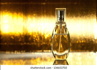 Bottle of perfume on abstract golden background