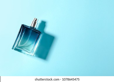 Bottle of perfume on color background, top view