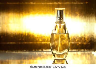 Bottle of perfume on shiny gold background