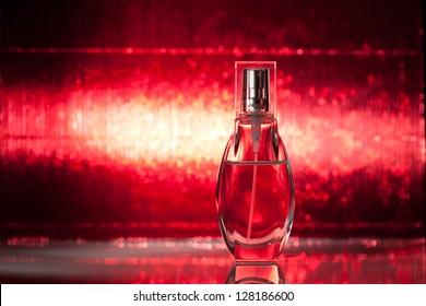 Bottle of perfume on shiny red background