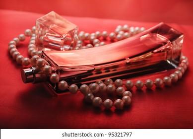 Bottle of perfume and pearls on purple silk