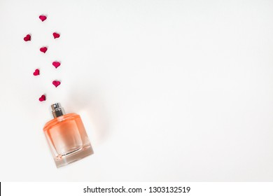 Bottle of perfume with red hearts flying out from it. Valentine's day, choosing fragrance, aroma of love concept with copy space.