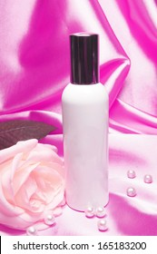 Bottle of perfume and rose with pearls on pink satin