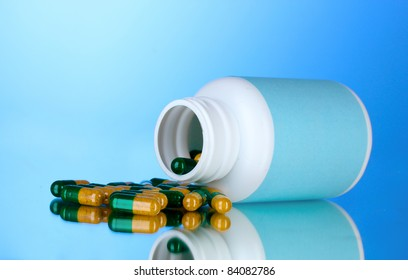 Bottle and pills on blue background