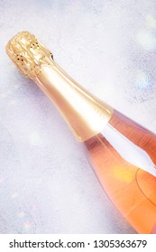 Bottle with pink sparkling wine or rose champagne and glasses, gray background with place for text, holiday or date concept, flat lay, top view vertical image