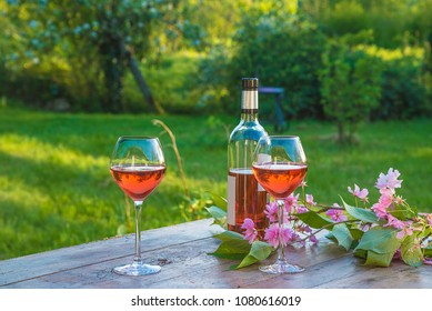 Bottle of pink wine and two wineglasses on a rustic wooden table