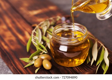 Bottle pouring extra virgin olive oil in a bowl copy space
