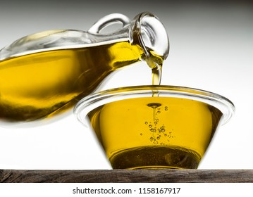 Bottle pouring olive oil in a bowl close up