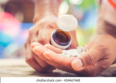bottle pouring pills on a male's hand