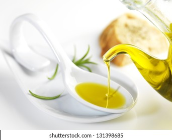 bottle pouring virgin olive oil in a porcelain spoon
