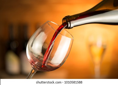 bottle pours red wine in a glass