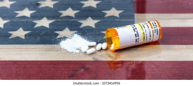 Bottle of prescription for Hydrocodone or generic opioid with crushed or whole pain killer tablets. Rustic USA flag in background for drug addiction concept in America