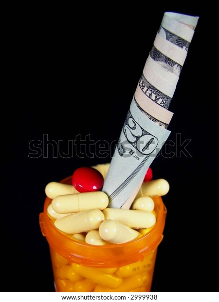 bottle of prescription pills with money isolated on black