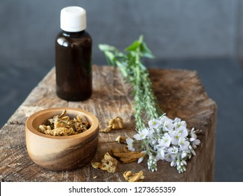 A bottle of propolis, flowers and wooden bowl and spoon of propolis granules on piece of wood.