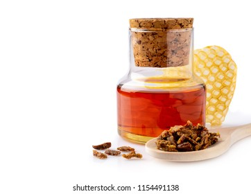 A bottle of propolis tincture and a wooden spoon of propolis granules. Medical preparations bee propolis. Isolated on white background. Bee glue. Apitherapy.