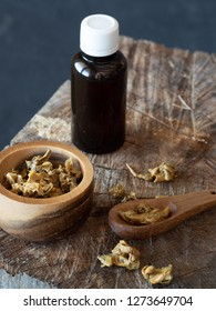 A bottle of propolis and wooden bowl and spoon of propolis granules on piece of wood.