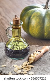 Bottle with pumpkin oil on the wooden background