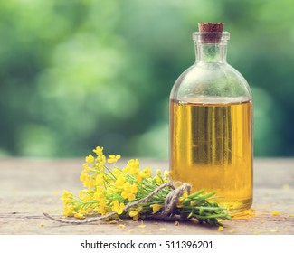 Bottle of rapeseed oil (canola) and rape flowers bunch on table outdoors