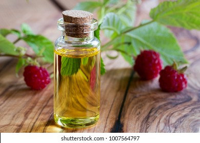 A bottle of raspberry seed oil with fresh raspberries in the background