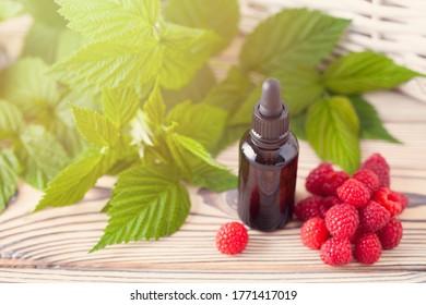 Une bouteille d'huile de framboise avec des fruits frais - traitement de beauté